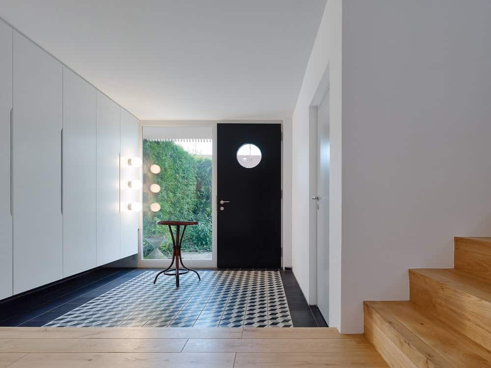 Upon entry of the house, you are welcomed by this simple foyer with a dark main door that matches the tone of the flooring tiles. By the window is the wooden table for displays.