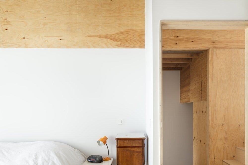 This is a view of the bedroom that showcases the proximity of the bed to the built-in wooden cabinetry that externds to the wooden beamed ceiling.