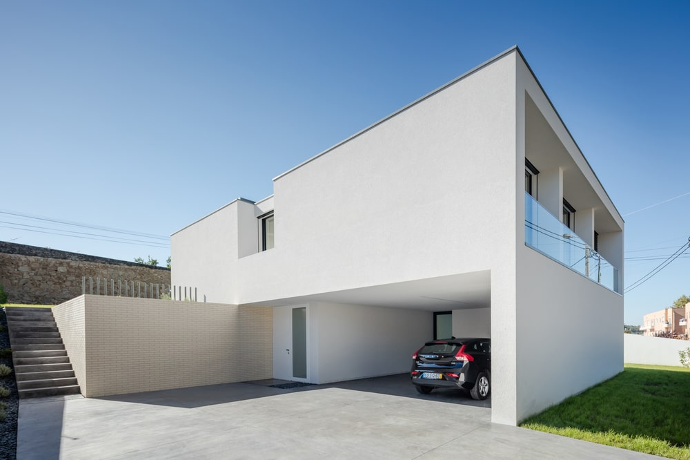 This minimalist home has a consistent light beige tone to its exterior walls with a car port on the ground level and a balcony on the upper level paired with glass.