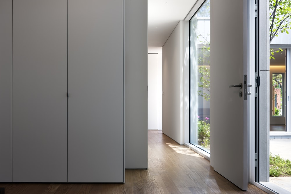 This is a view of the glass walls from the vantage of the hallway that has a hardwood flooring contrasted by the white walls.
