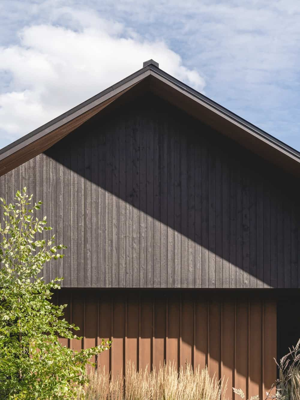 This is a close look at the dark wooden exterior wall of the house along with the A-frame roof of the house.