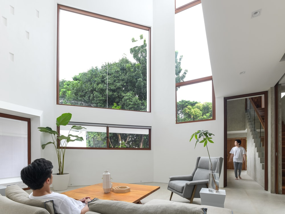 The living room has a spacious area and tall ceiling complemented by the natural lighting that comes in from the glass windows.
