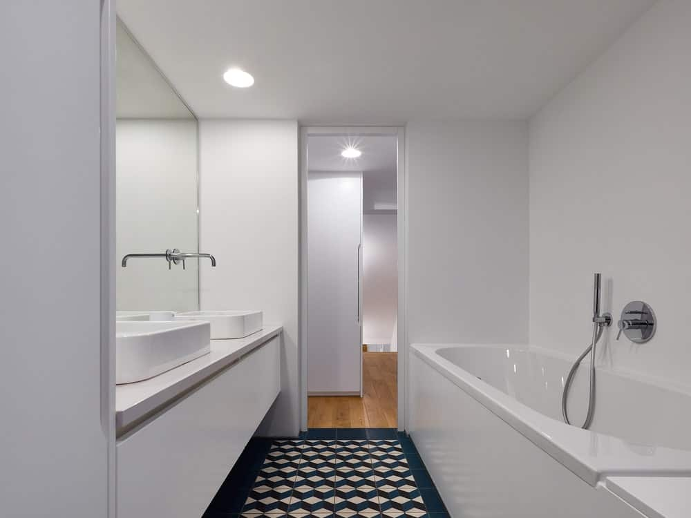 The bathroom has a large bathtub across from the bright beige modern sink topped with a large wall-mounted mirror.