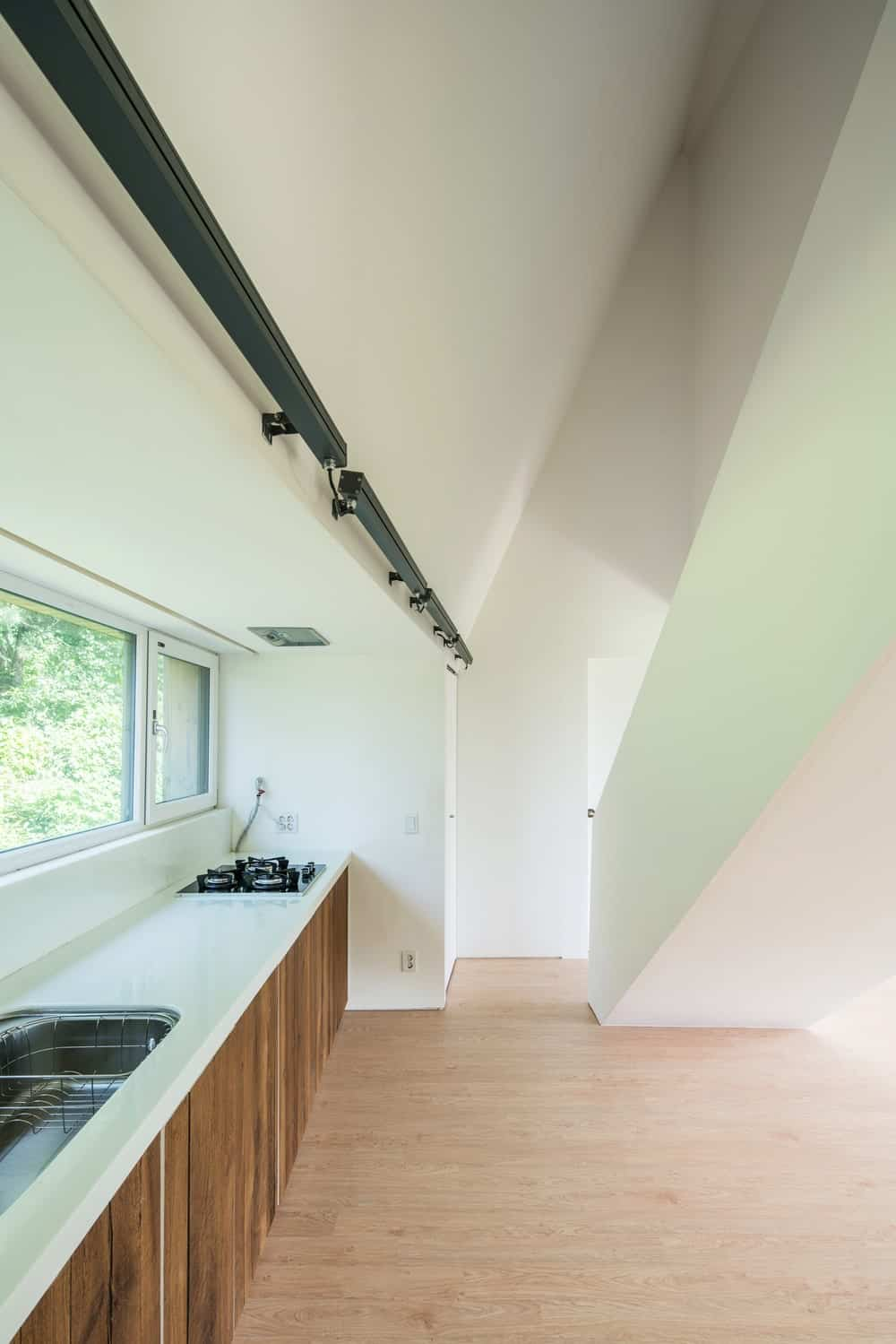 The kitchen has a simple counter by the windows that supports the cabinetry that has wooden cabinets by the saircase.