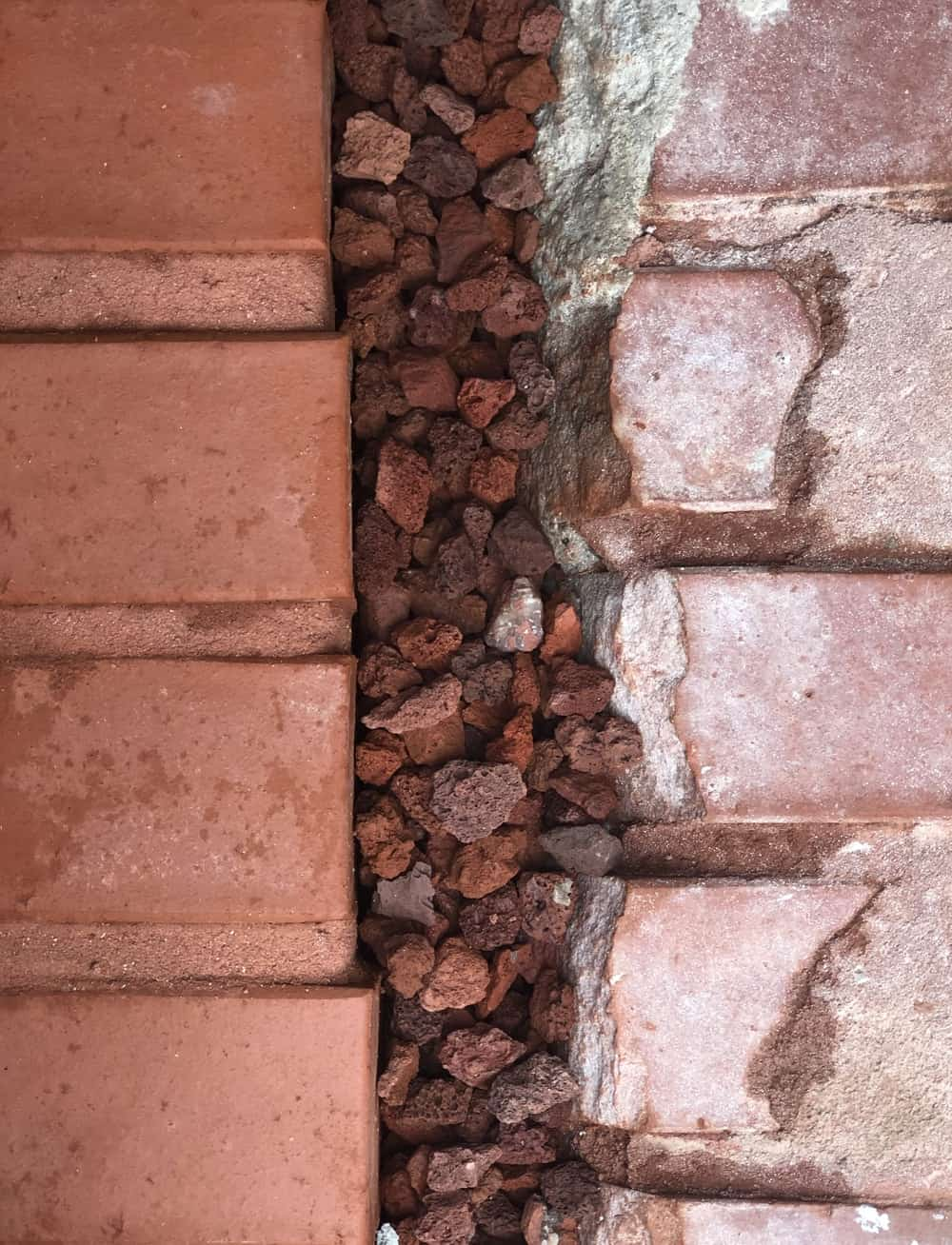 This is a close look at the red brick walls and gravel of the house exterior giving it a layered look.