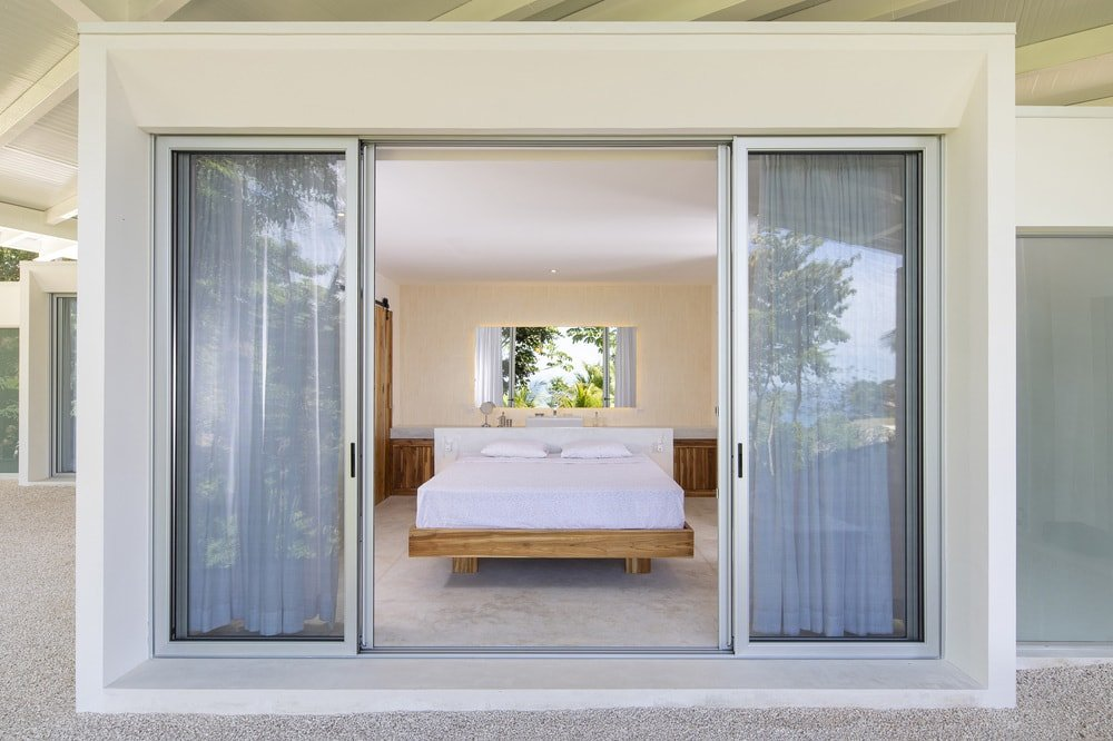This is aview of the bedroom from the vantage of the outdoor area outside its open glass doors looking into the beige walls of the interior.