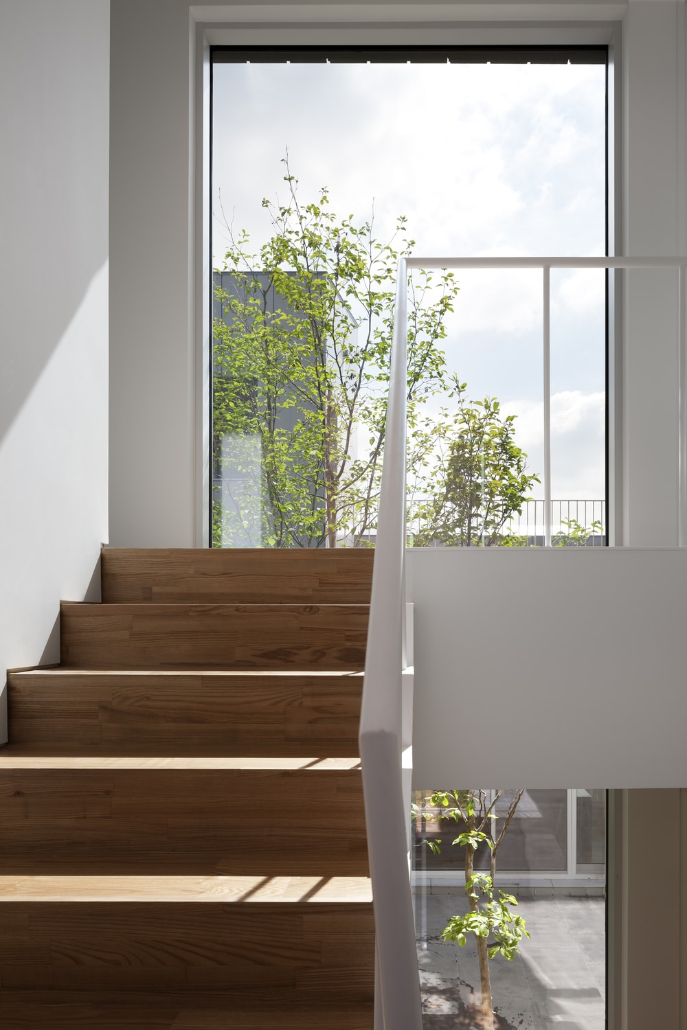 This is a closer look at the stairs and the second-level landing that is brightened by the natural lights of the glass wall.