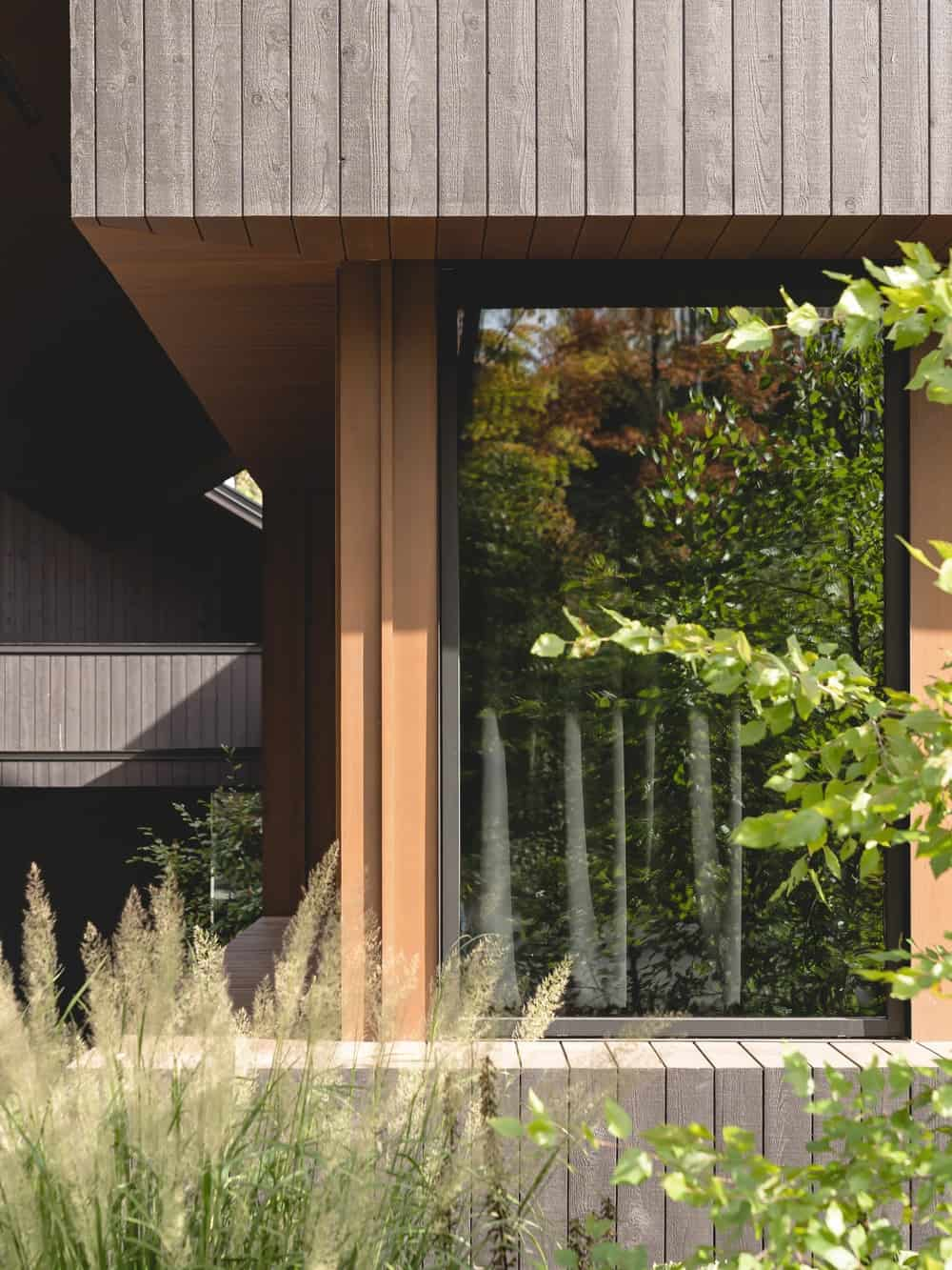 This is a close look at the exterior corner of the house with glass walls and wooden support beams.