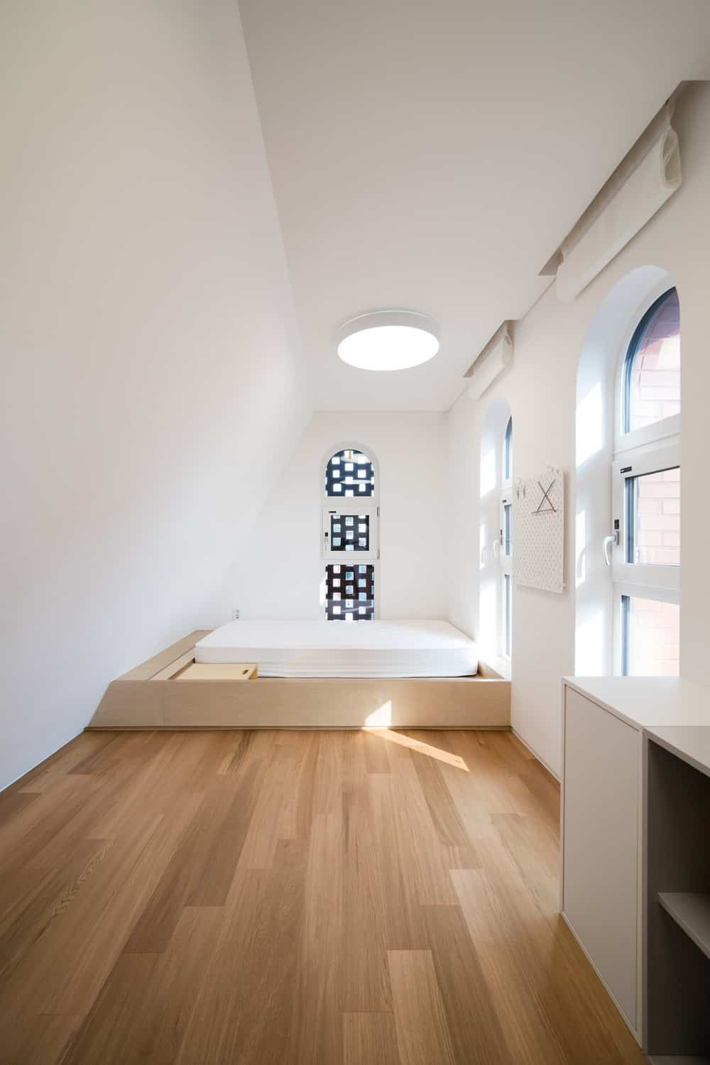 This bedroom has a wooden platform bed on the far side by the windows. This is complemented by the surrounding bright beige walls and ceiling.