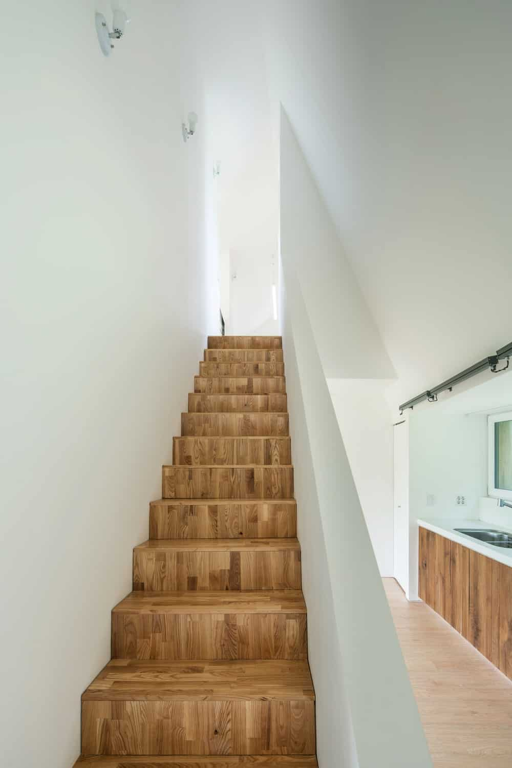 This is a close look at the wooden steps of the stairscase that makes it stand out against the bright walls on both sides.