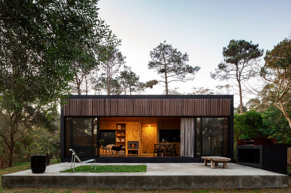 This home has dark brown slatted exterior walls that pair well with the warm interiors that escape through the large opening.