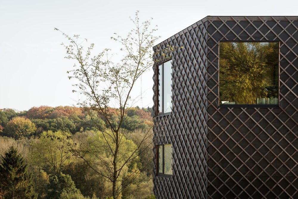 This is a closer look at the textured exterior dark walls of the house that makes the bright and shiny glass windows to stand out.