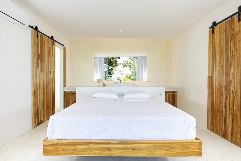 The beige walls of the bedroom is complemented by the wooden barn doors that match well with the floating wooden platform bed.