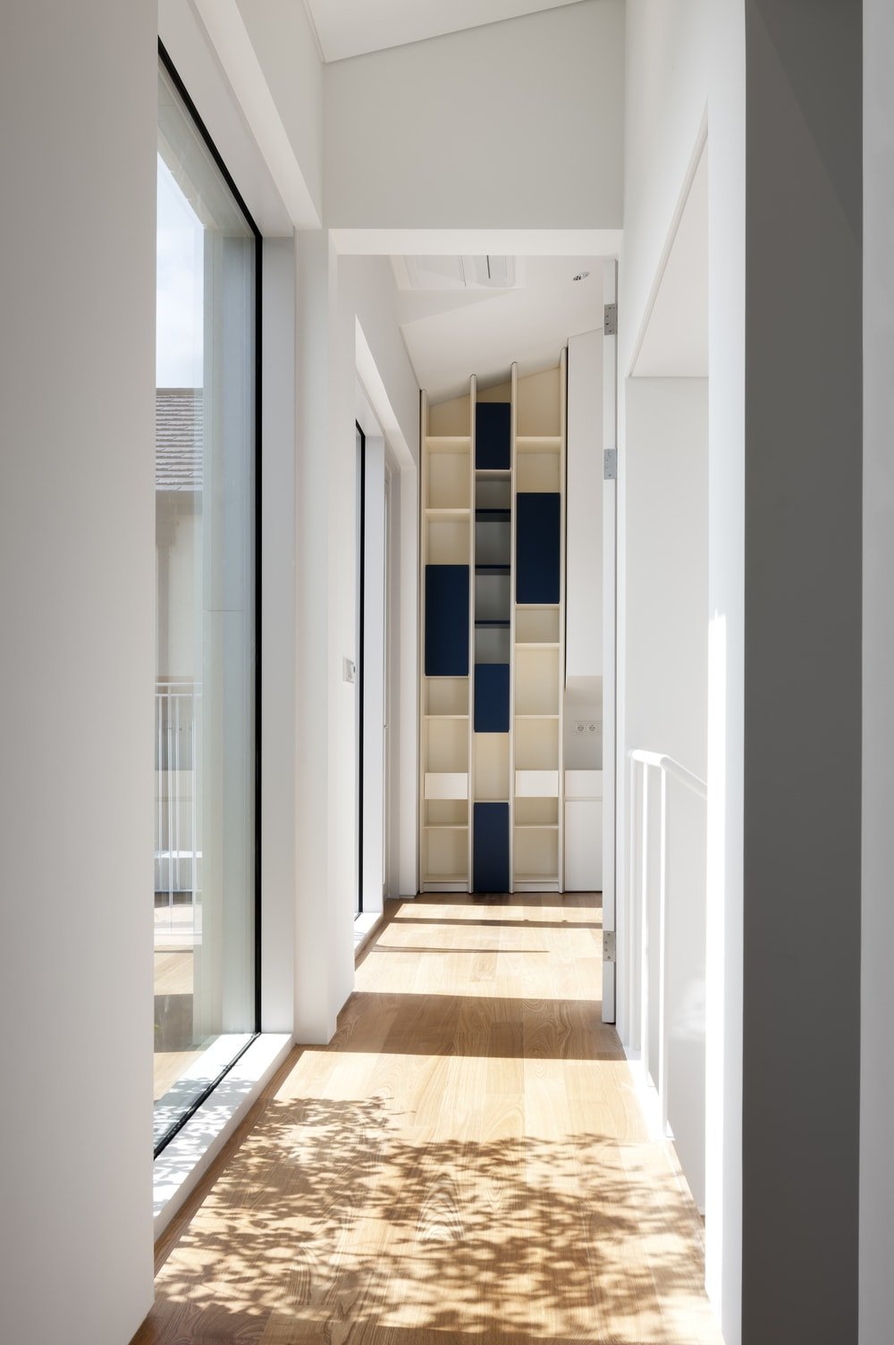 This is a hallway on the upper level of the house that has glass walls and built-in shelf system on the far end.