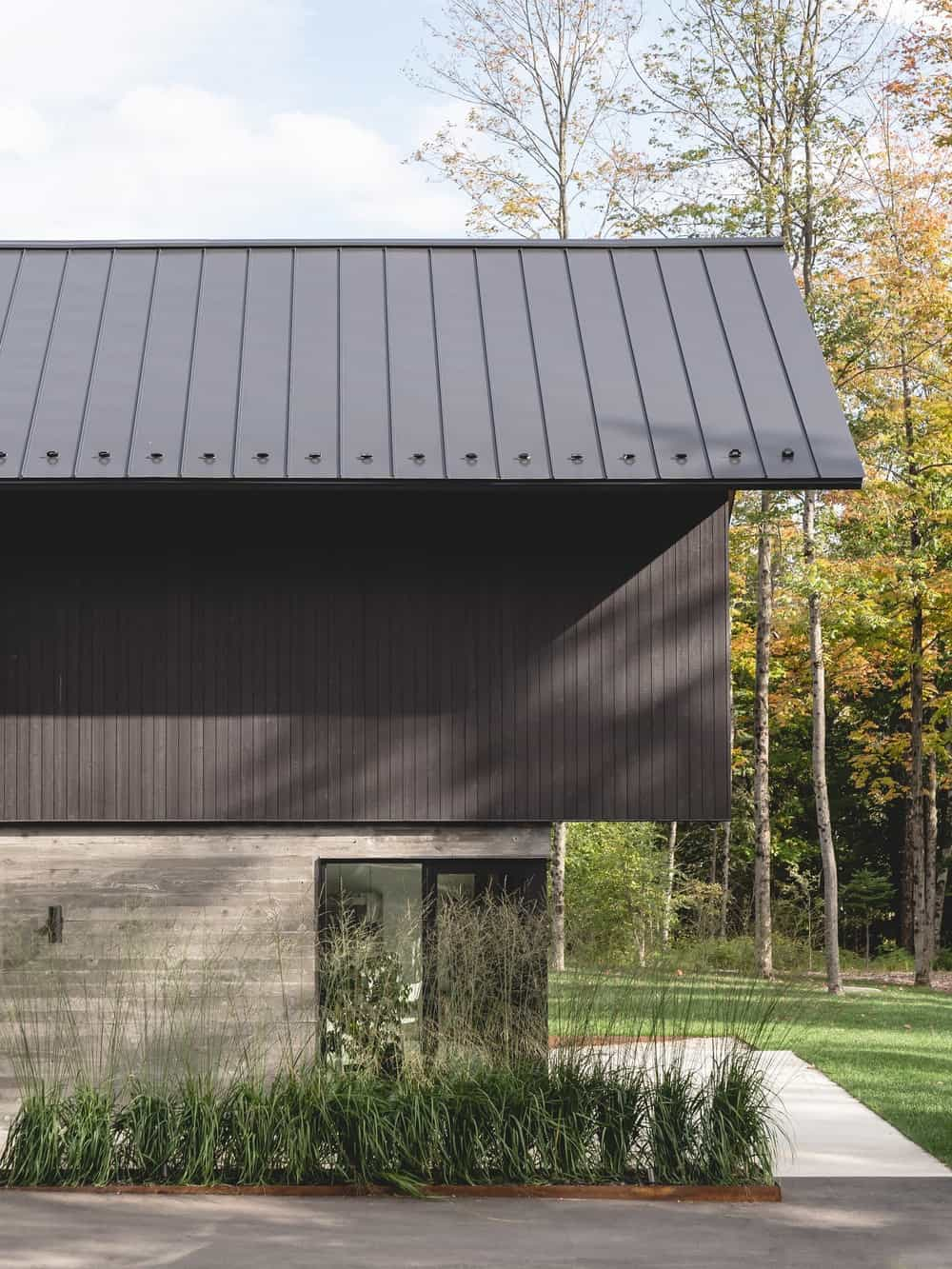 This is a close look at the main entrance of the house that has dark exterior walls on its upper levels and concrete at the base that makes the glass main door stand out.