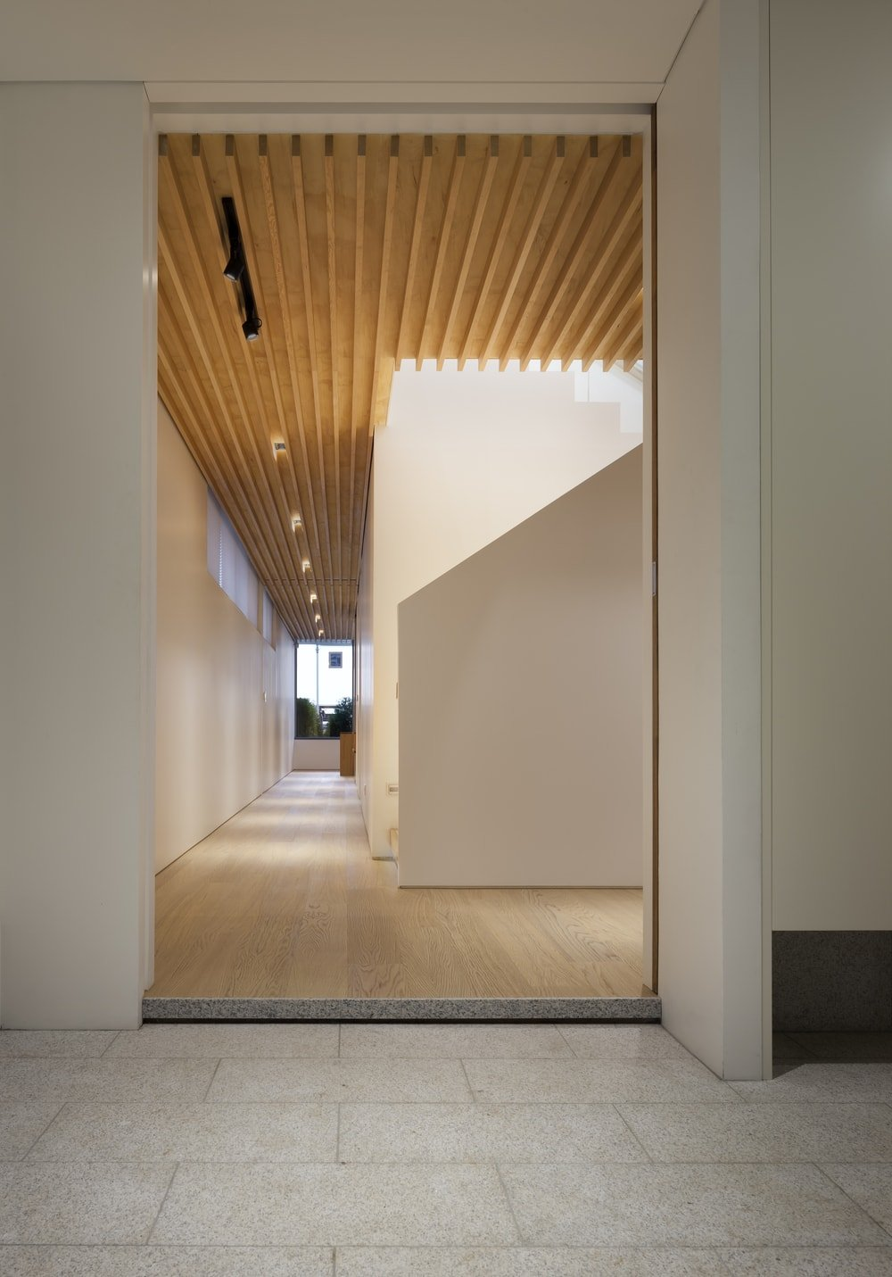 This view of the interior features the wooden beamed ceiling with modern lighting over the hardwood flooring.