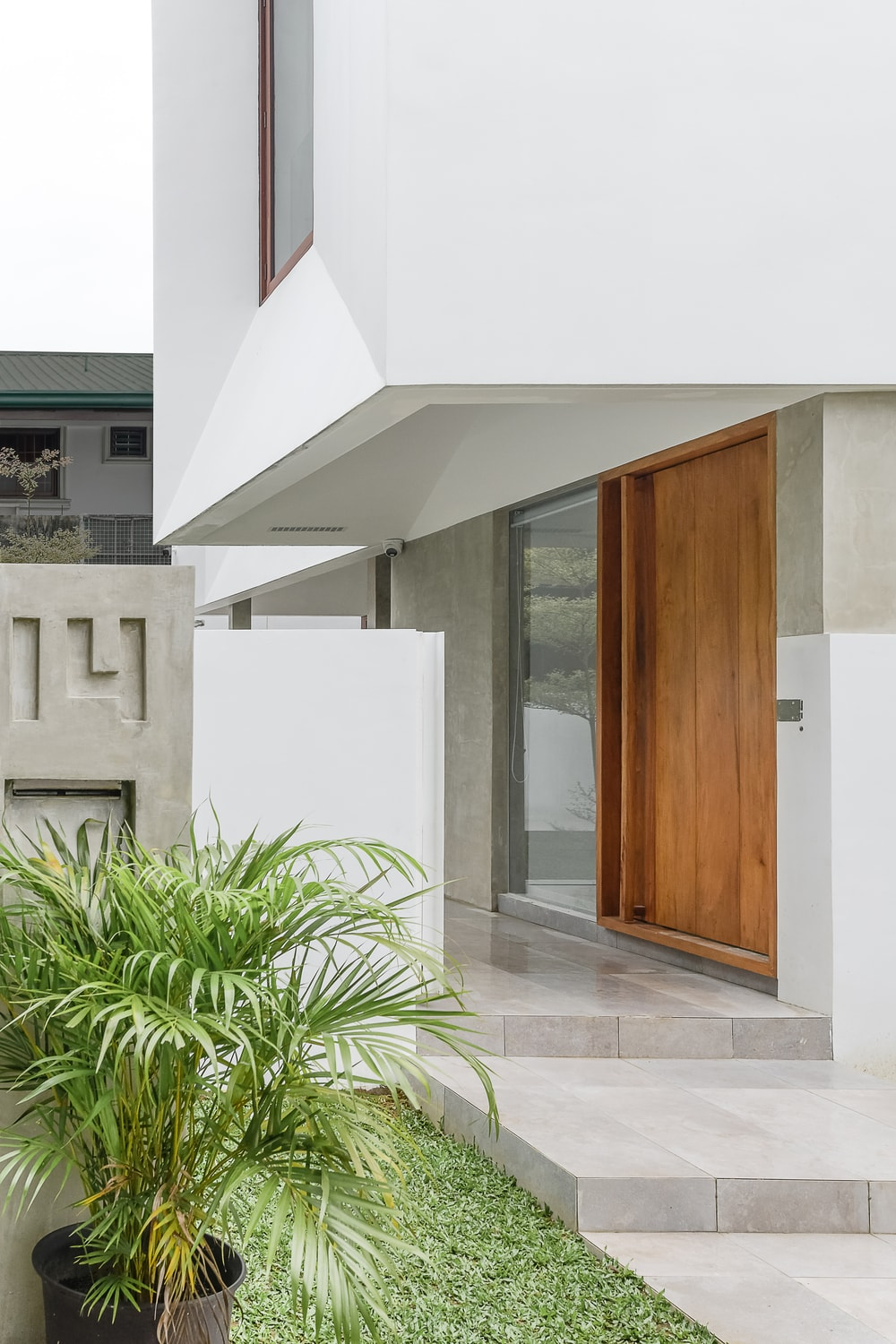 This is a close look at the main door of the house with a large wooden door that has a glass wall on the side.