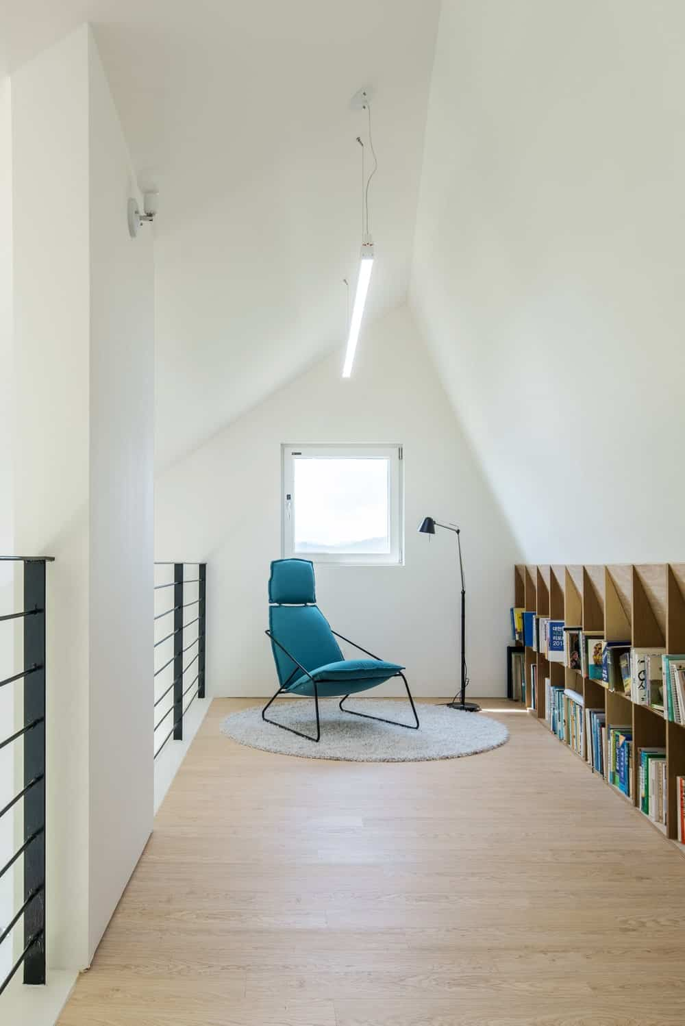 This is a look at the attic library that has a wooden structure built into the wall on the side for books. This is paired with a comfortable chair by the window and lamp.