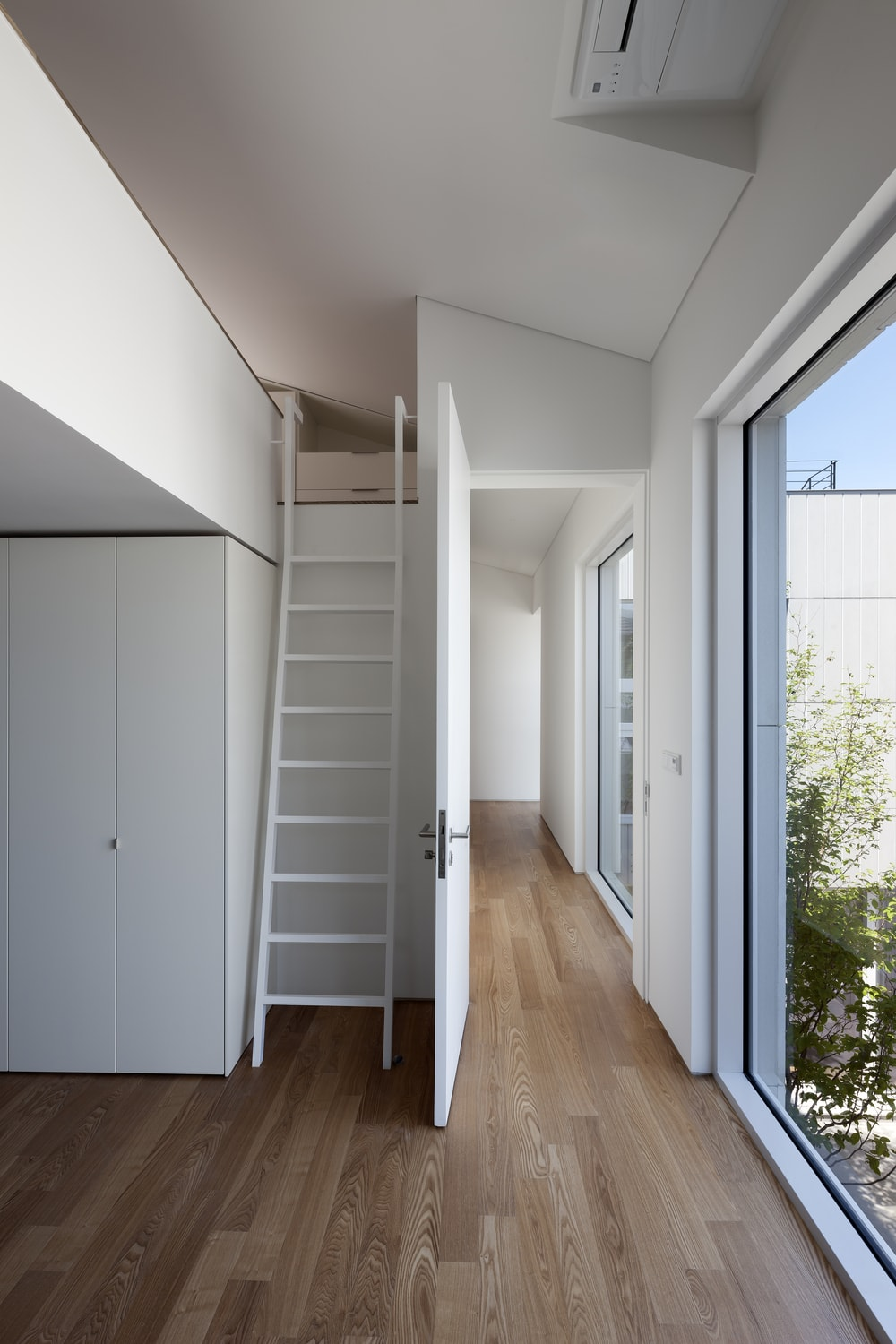 This is a corner of the house that has a ladder to access the upper level of the house with a low ceiling that matches the walls.