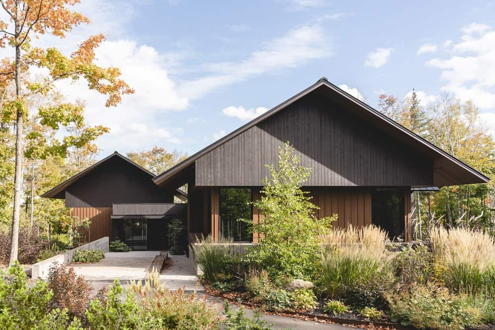 This is a look at the exterior of the house that has dark wooden exteriors that match well with the surrounding lush landscape of trees and shrubs that bring color to the exteriors.