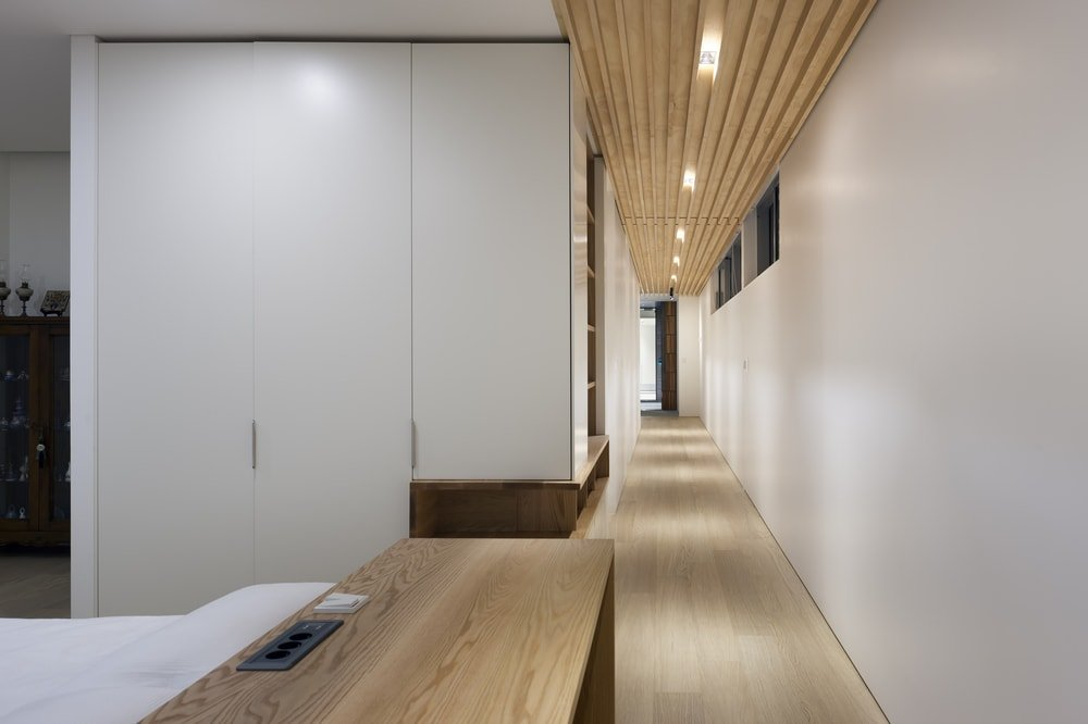This is a long hallway behind with bright beige walls and doors on the side that are complemented by the wooden beamed ceiling and hardwood flooring.