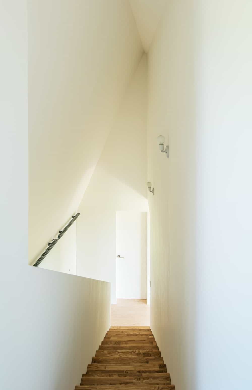 This is a look down the staircase showcasing the tall bright walls over the stairs.