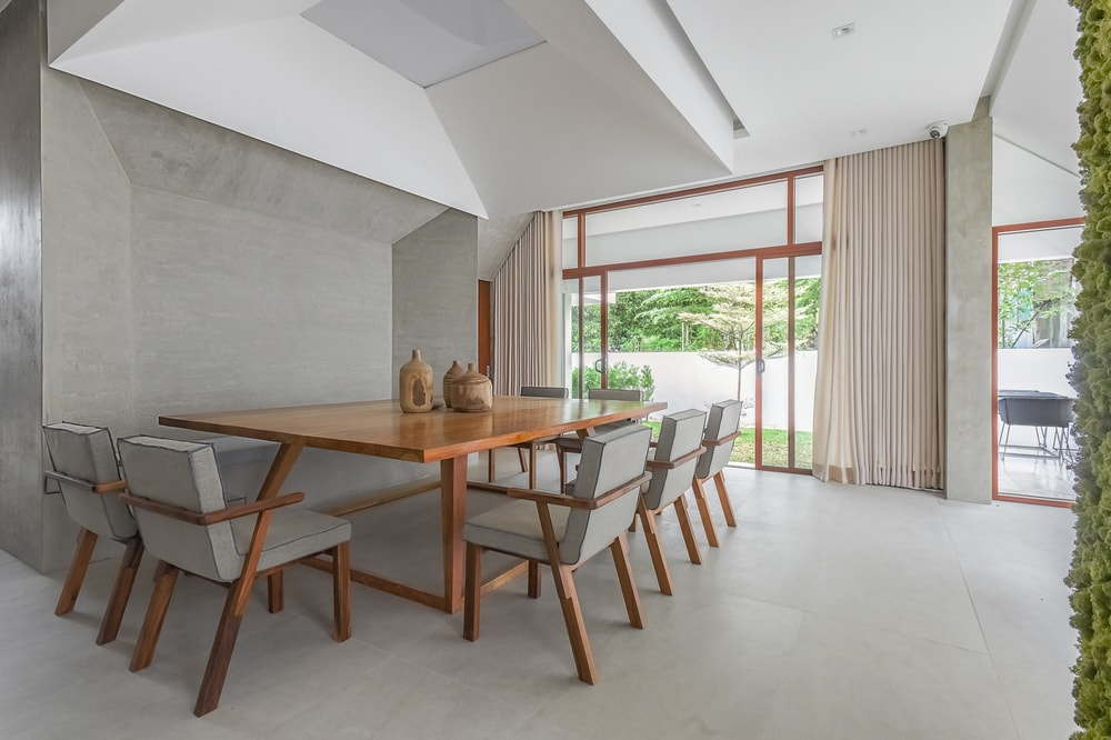 The bright dining room has a large wooden dining tabe paired with wooden chairs adorned by gray cushions.