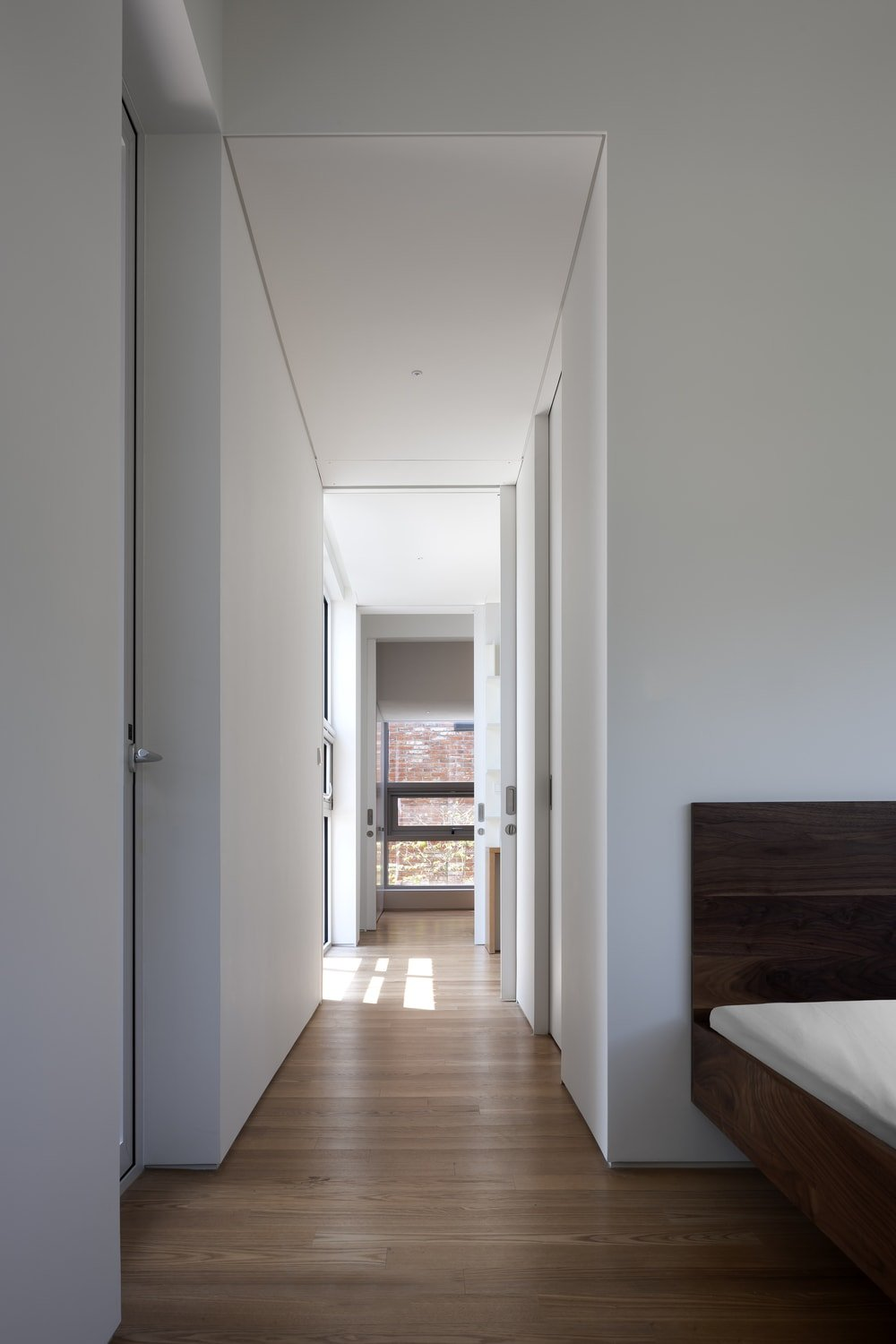 This is a look at the bedroom with a large wooden floating platform bed that is slightly darker than the hardwood flooring.