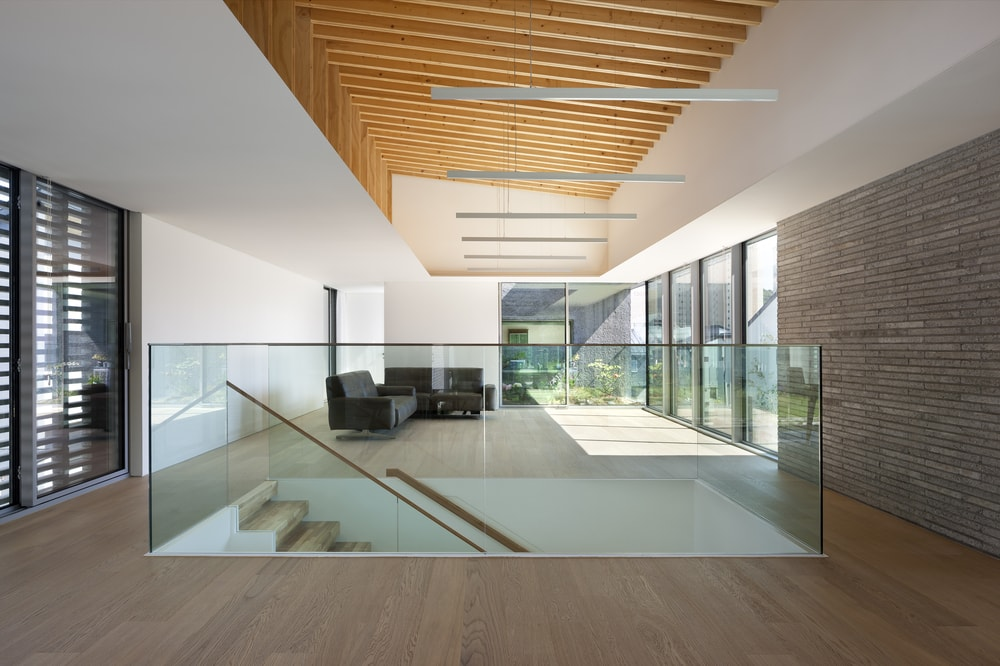 This closer look at the low glass walls of the staircase also gives a view of the dark sectional sofa of the living room that has an abundance of natural lighting.