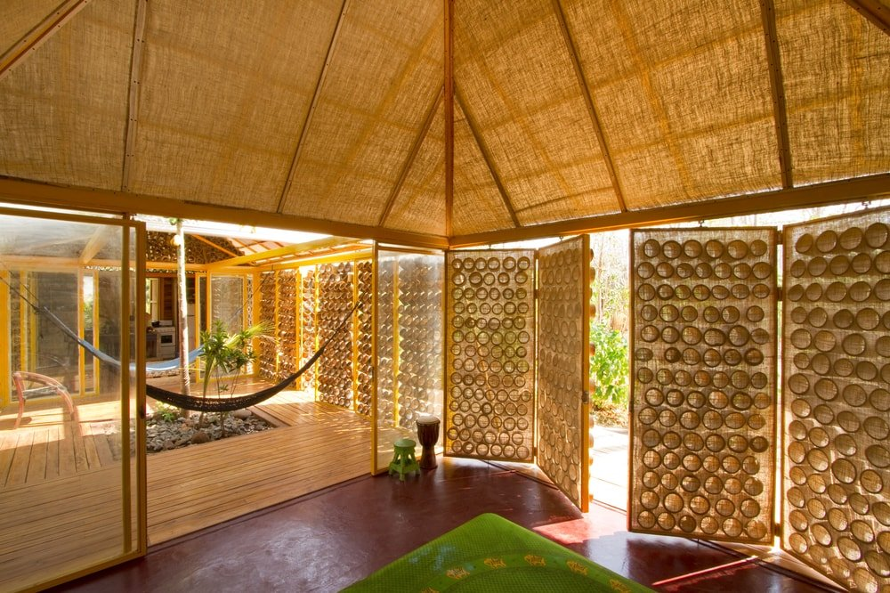 This is a look at the interior that has a terracotta tone to its flooring that transitions to a wooden walkway in the middle where there is no roof.