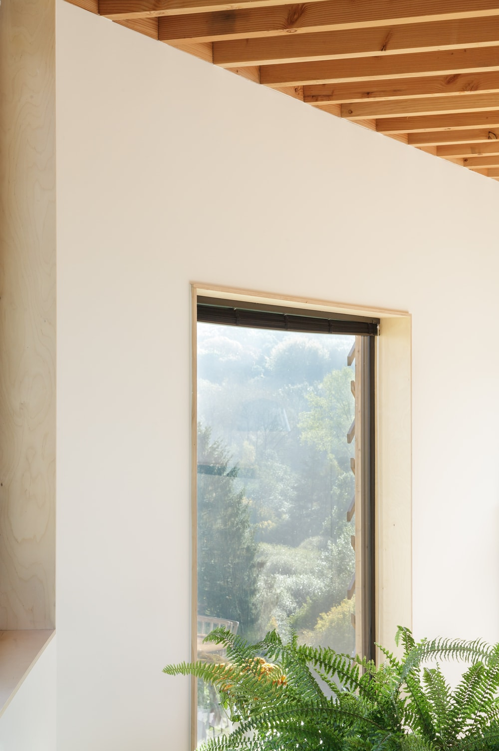 This is a close look at one of the glass windows that stand out against the surrounding beige walls and wooden beamed ceiling.