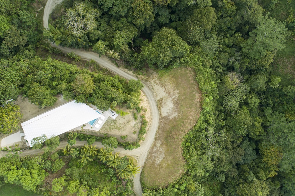 This is a farther aerial view of the house and its surrounding landscape.