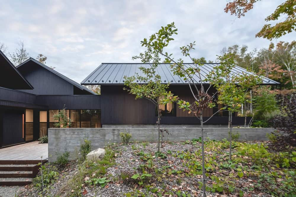 This side of the house has a low concrete wall and concrete steps that make it contrast against the dark walls and dark roofs.