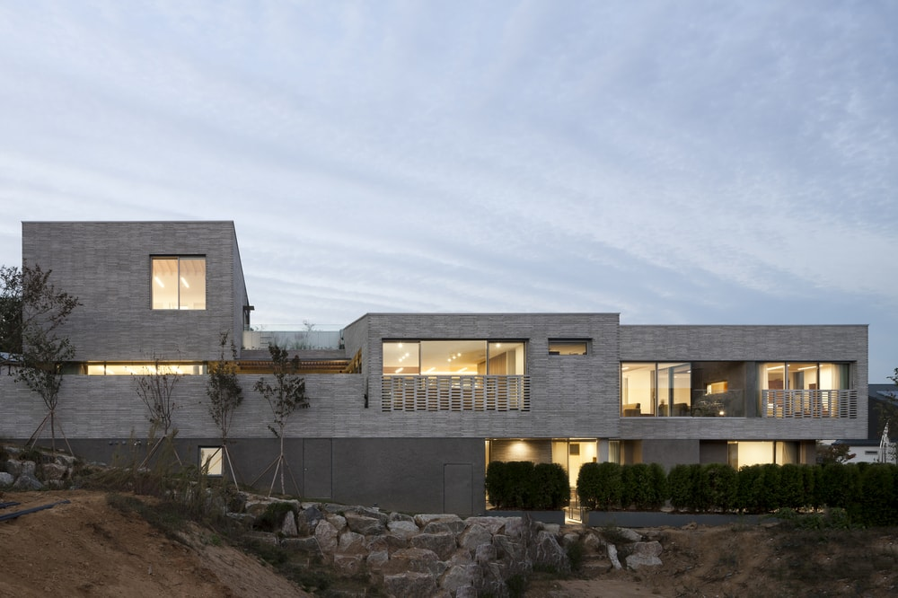 This is a full view of the house exterior showcasing the warm glow of the windows and balconies.
