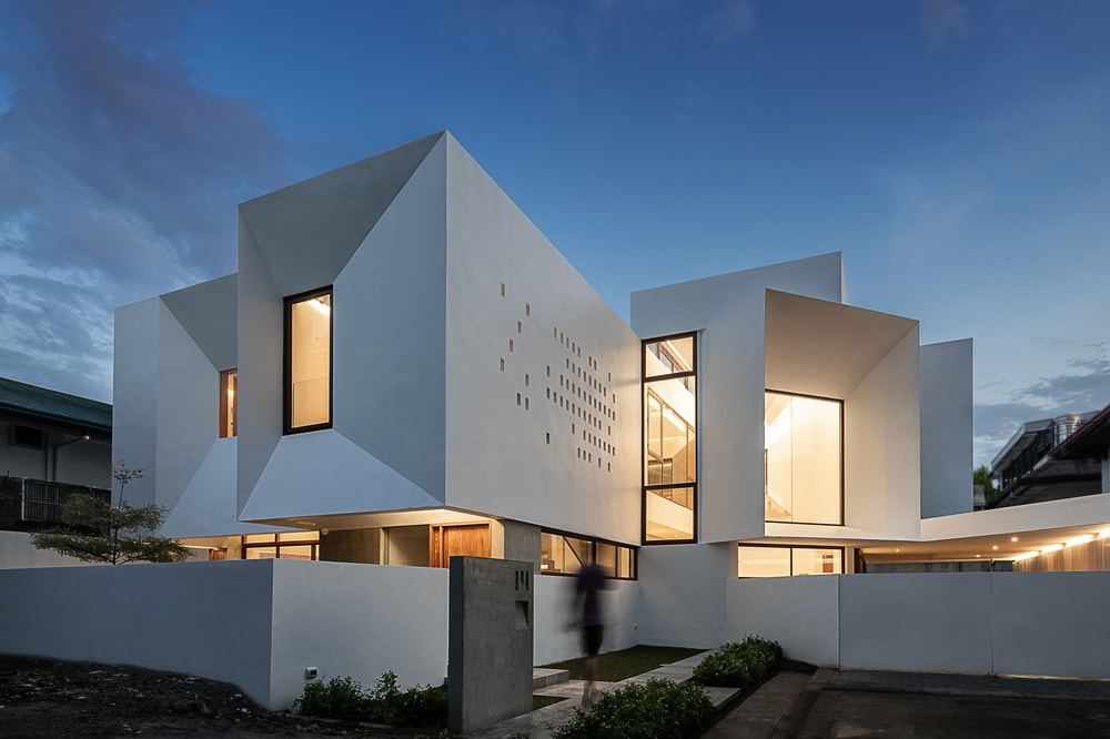 This is the front view of the house exterior that has consistent bright white exterior walls complemented by the unique windows that glow warmly and wall patterns. These walls match with the outer walls of the house that has a dark gate.