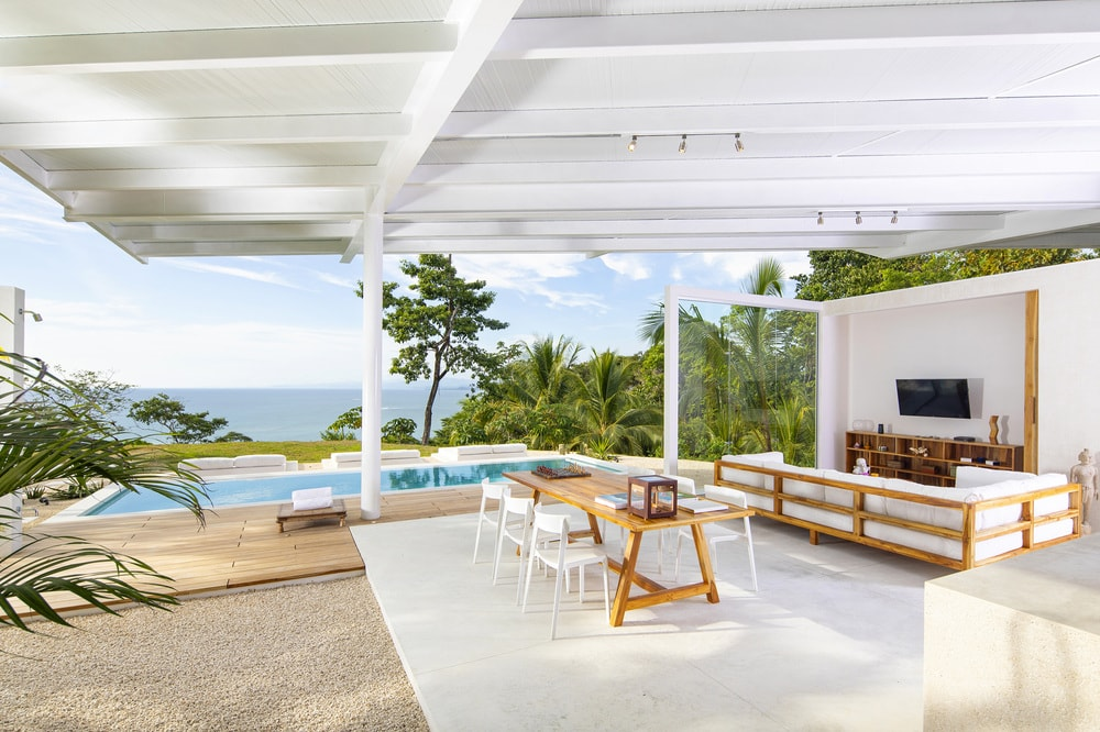 This is the open patio with a clear view of the swimming pool on the far side. This houses a dining area and a living room area.