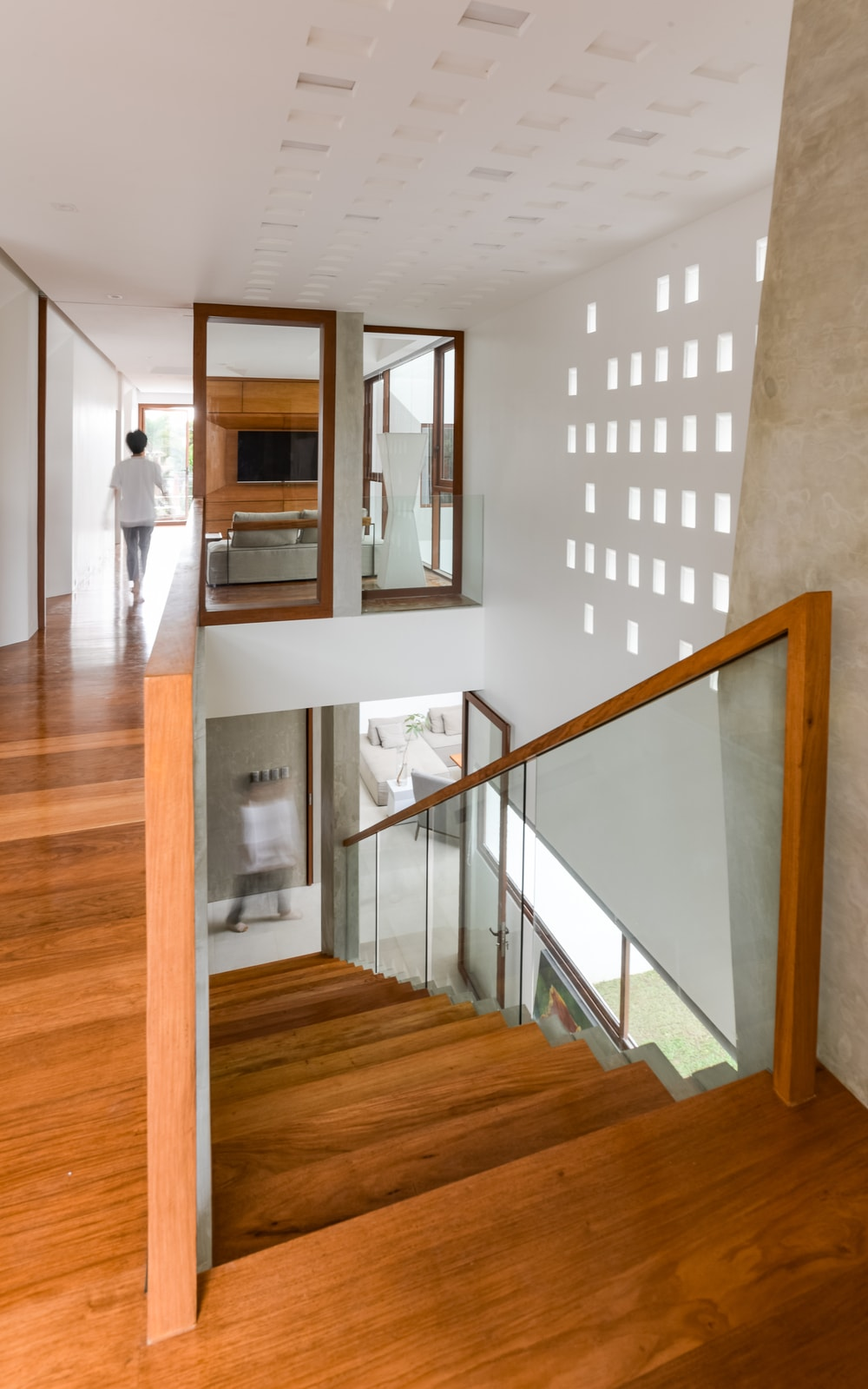This is the view of the second-level landing showcasing the wooden steps of the stairs that matches with the hardwood flooring and banisters.