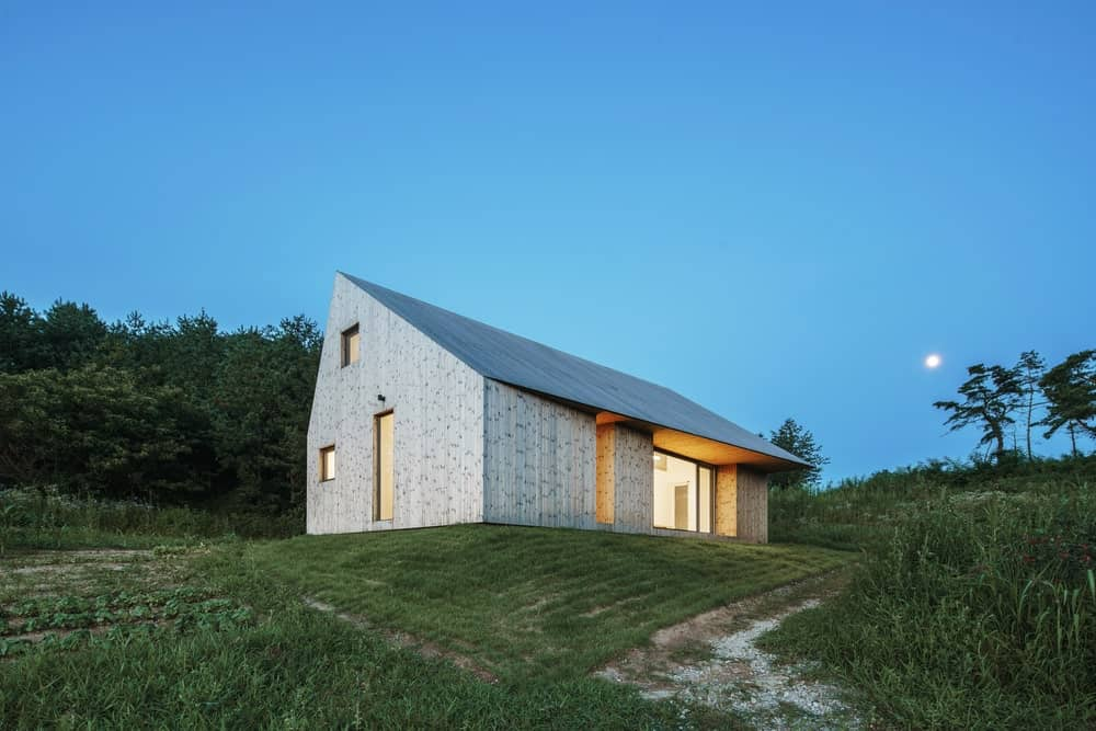 This is a nighttime exterior look at the house with simple patterns and a ceiling over the glass wall of the side.