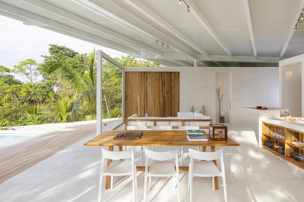 This is a close look at the dining area that has a wooden rectangular dining table paired with with chairs.