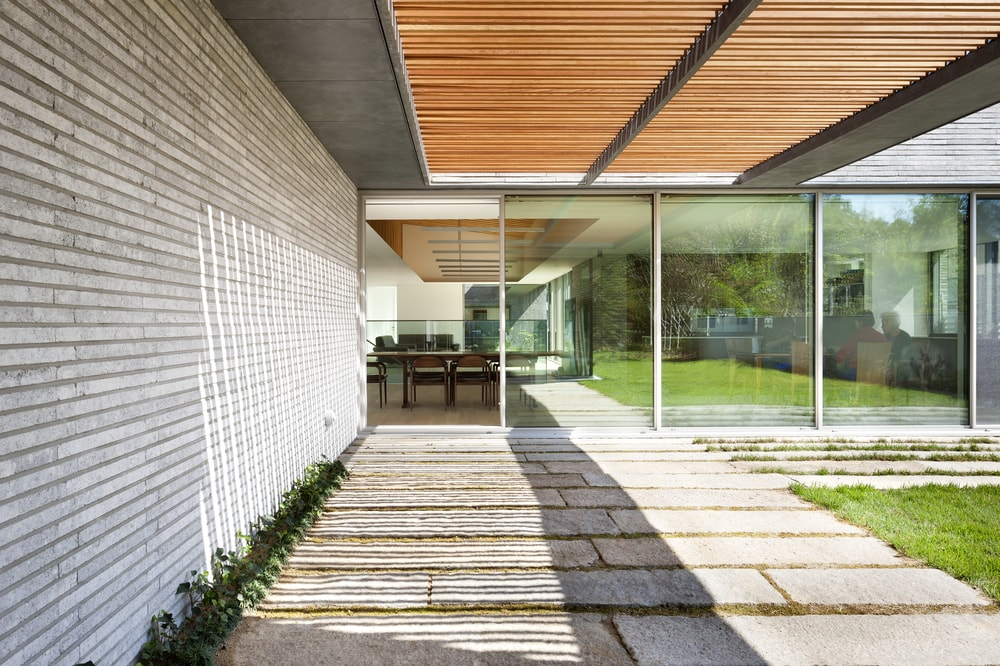This is a closer look at the covered and shaded walkway with a set of slat wooden panels on the ceiling for a shaded effect that leads to the other glassed section of the house.
