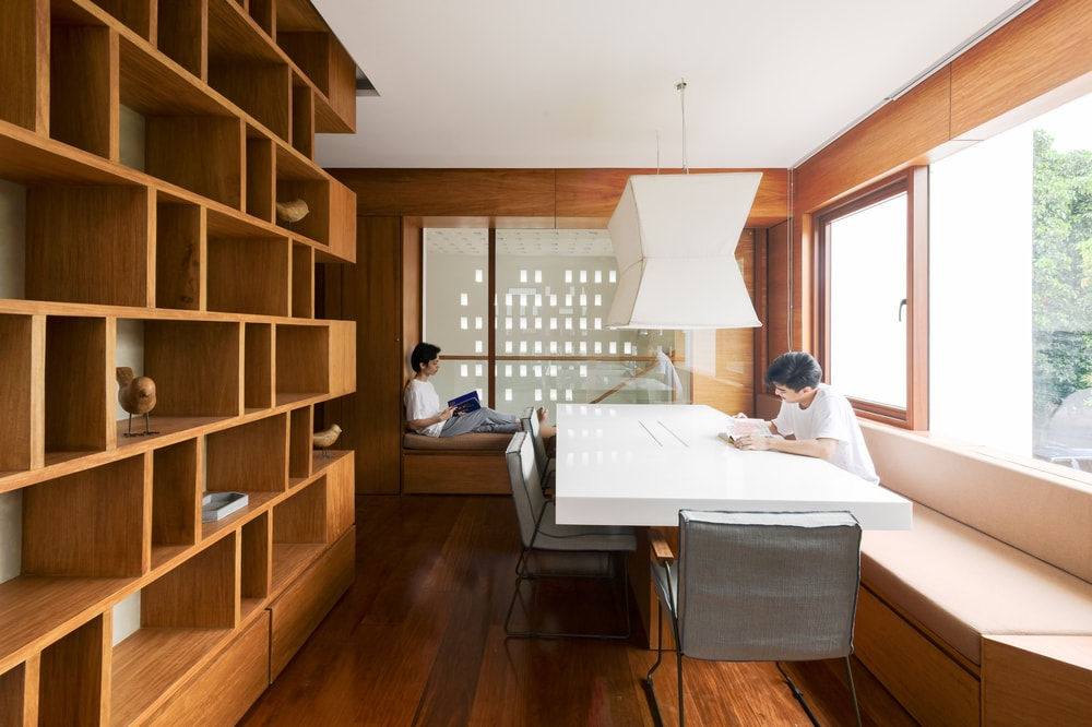 This is the airy and bright library with a large built-in wooden structure for book across from the large study table and a reading nook on the far side.