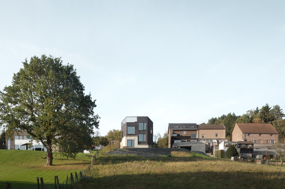 This is a view of the house from a distance showcasing the surrounding area and landscape with tall trees and grass lawns.
