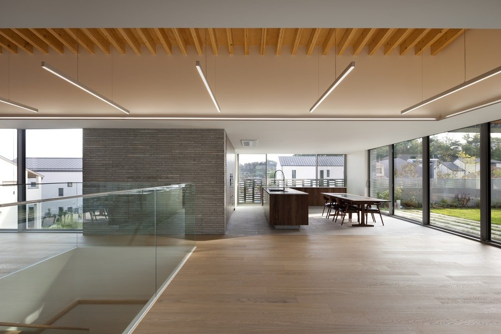 This is a look at the kitchen and dining area of the house with a large L-shaped kitchen island that matches with the long wooden dining table.