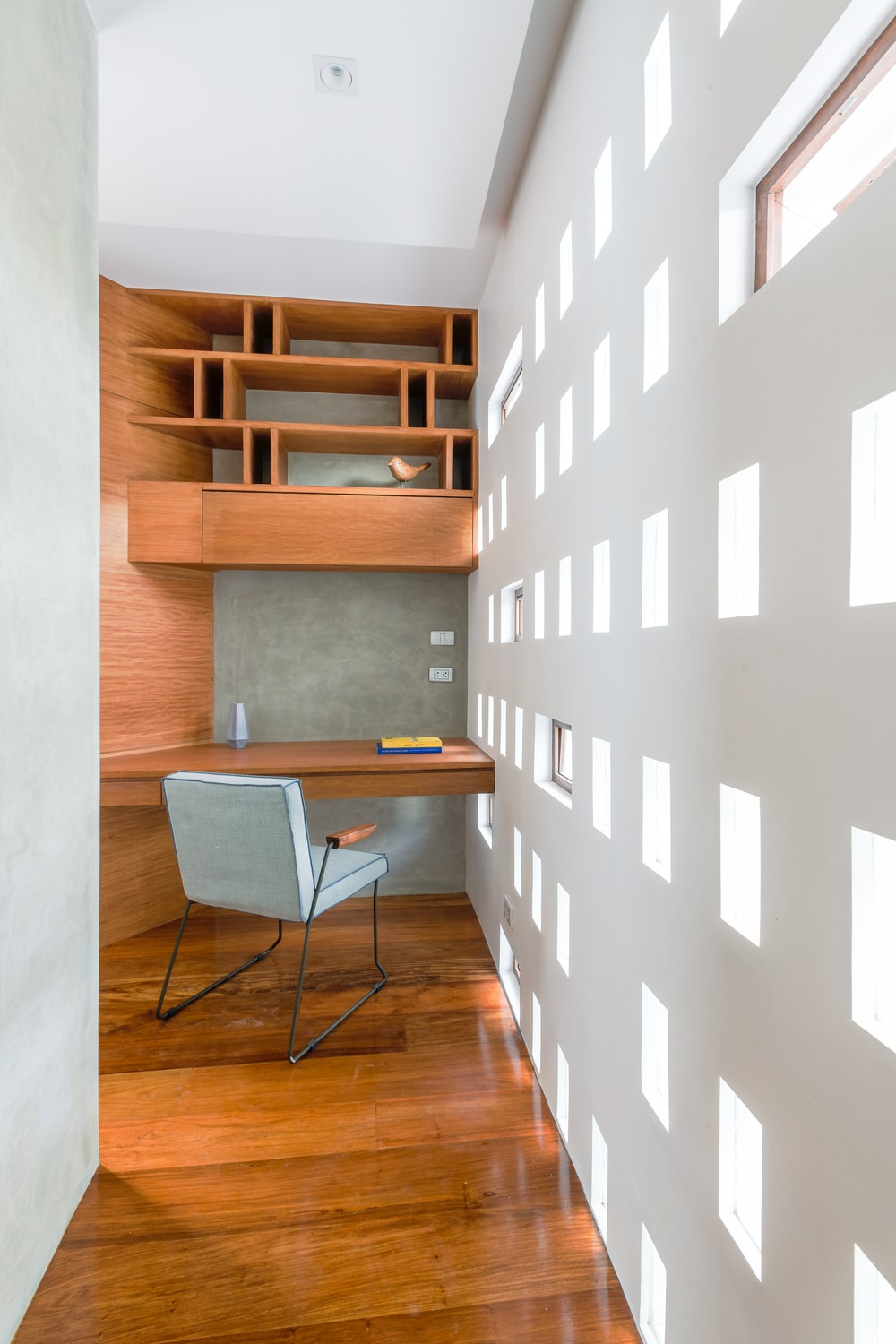 This is a close look at the study area of the house that has built in wooden wooden structures as desk and shelves above.