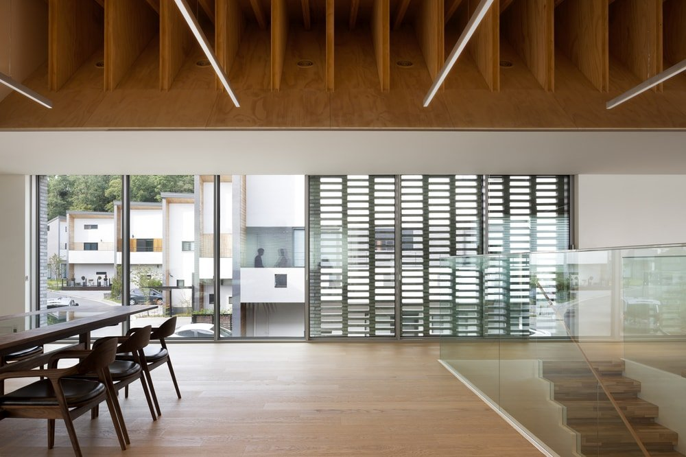 This view of the house showcases the dining table, glass-enclosed staircase and the large wooden beamed ceiling above.