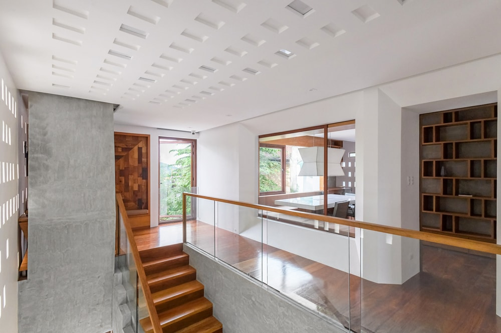 The second level landing and the indoor balcony with glass walls that also showcase the decorative wooden panel and built-in wooden shelves.