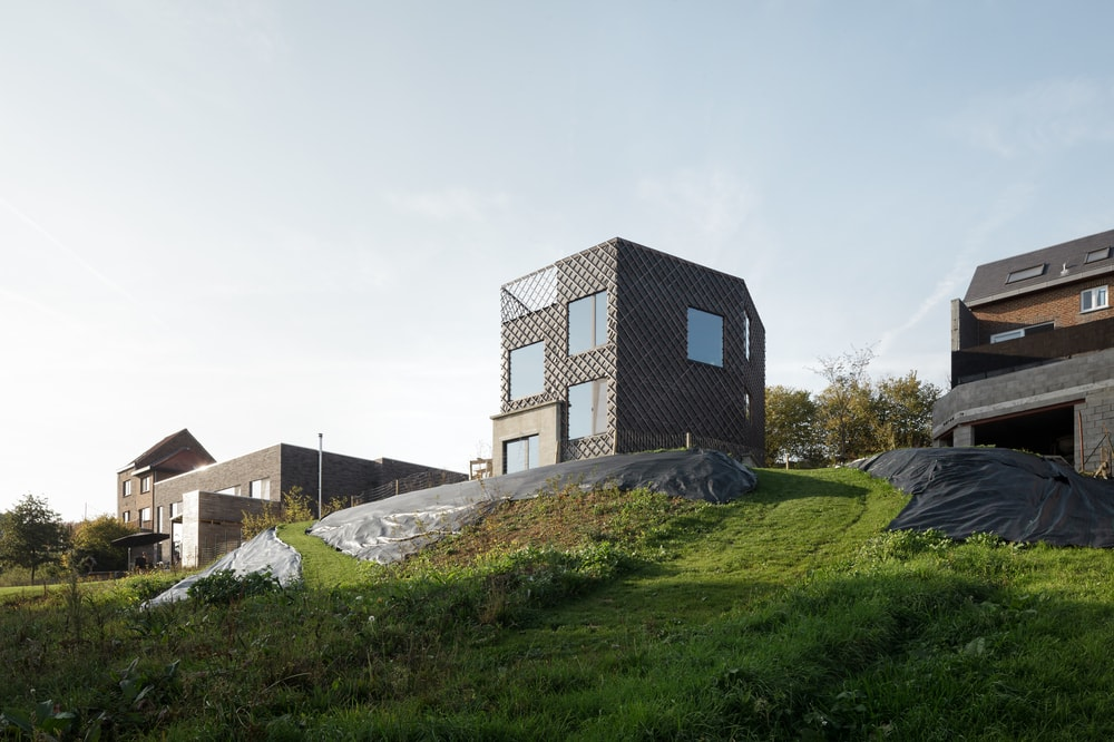 This is a view of the house on top of the hill with a patterned and textured dark gray exterior walls that make the glass walls stand out.