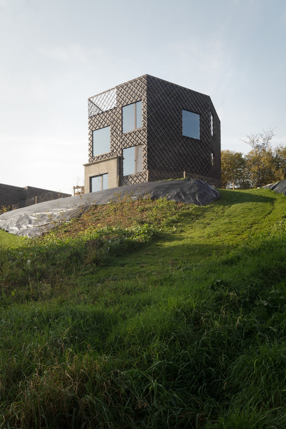 This is a closer look at the house showcasing the elevated landscape of the hill it is built on.