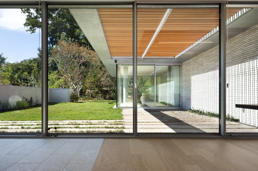 This is a view of the grass lawn and walkway of the back of the house from the vantage of the glass wall.