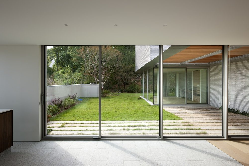 The glass walls can be retracted that can open the interiors to the grass lawn of the backyard.